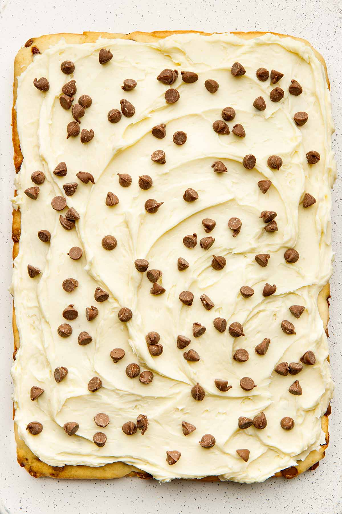 A cake with frosting and chocolate chips.