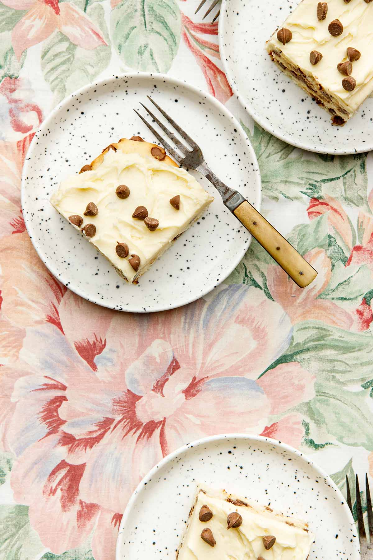 Three slices of chocolate chip cake on plates on a flowered tablecloth.