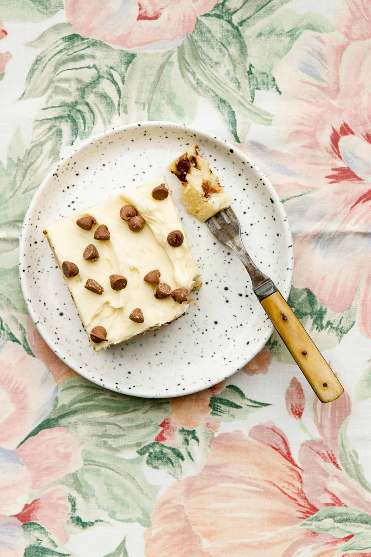 A slice of chocolate chip cake on a plate on a flowered tablecloth.