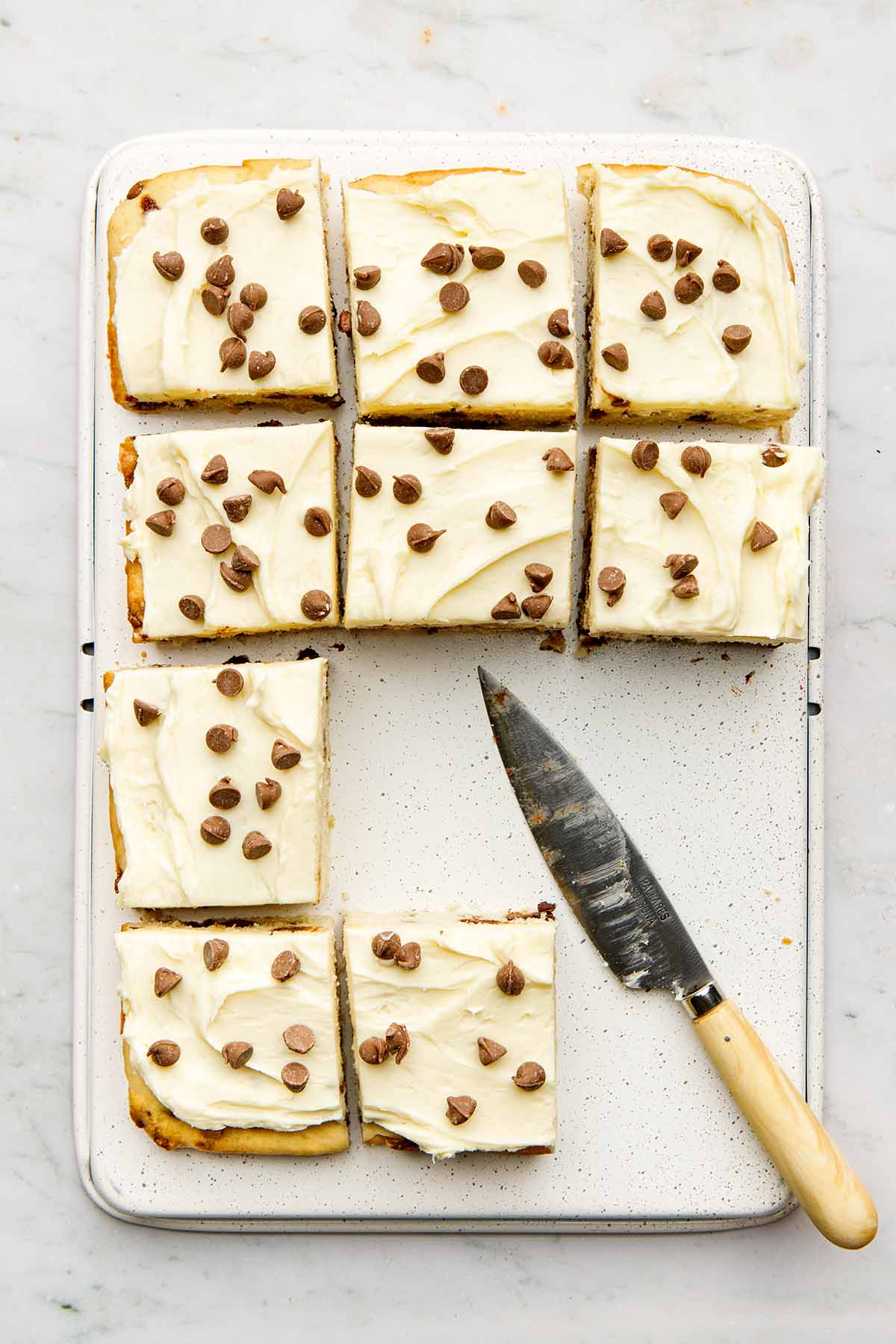 A chocolate chip sheet cake cut into squares on an upsie down baking tray with a knife nearby.