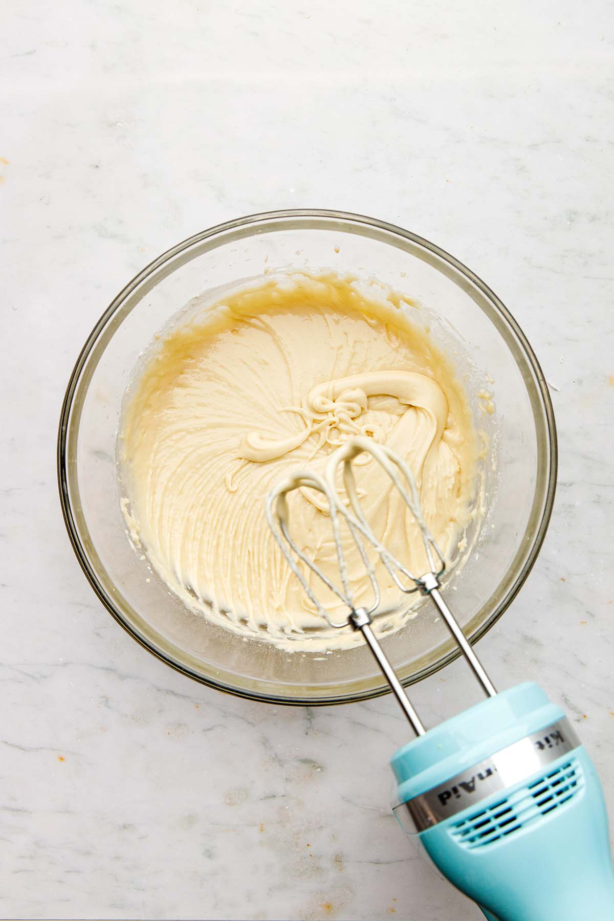 Mixed cake batter in a bowl with a hand mixer nearby.