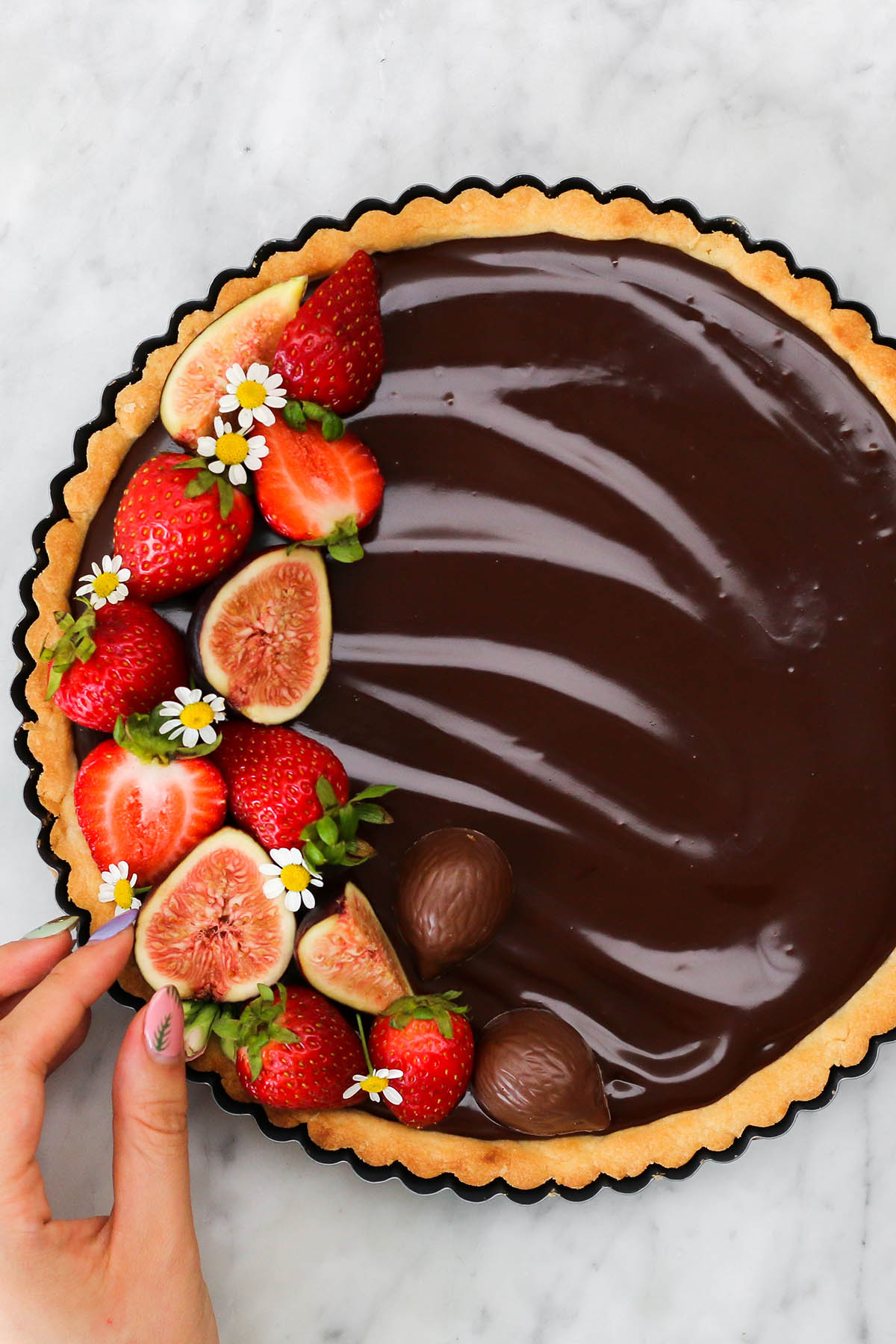 A hand placing fruit on top of a chocolate ganache tart.