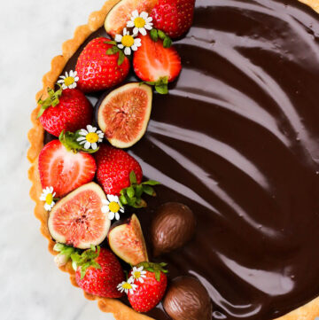 A chocolate ganache tart decorated with fresh fruit and chamomile blossoms.