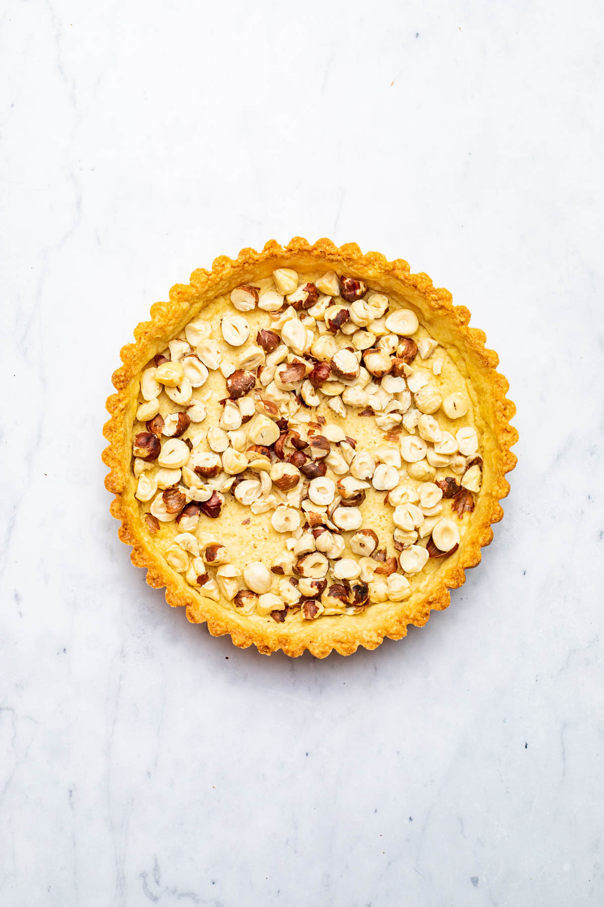 A pastry shell with toasted hazelnuts scattered over the bottom.