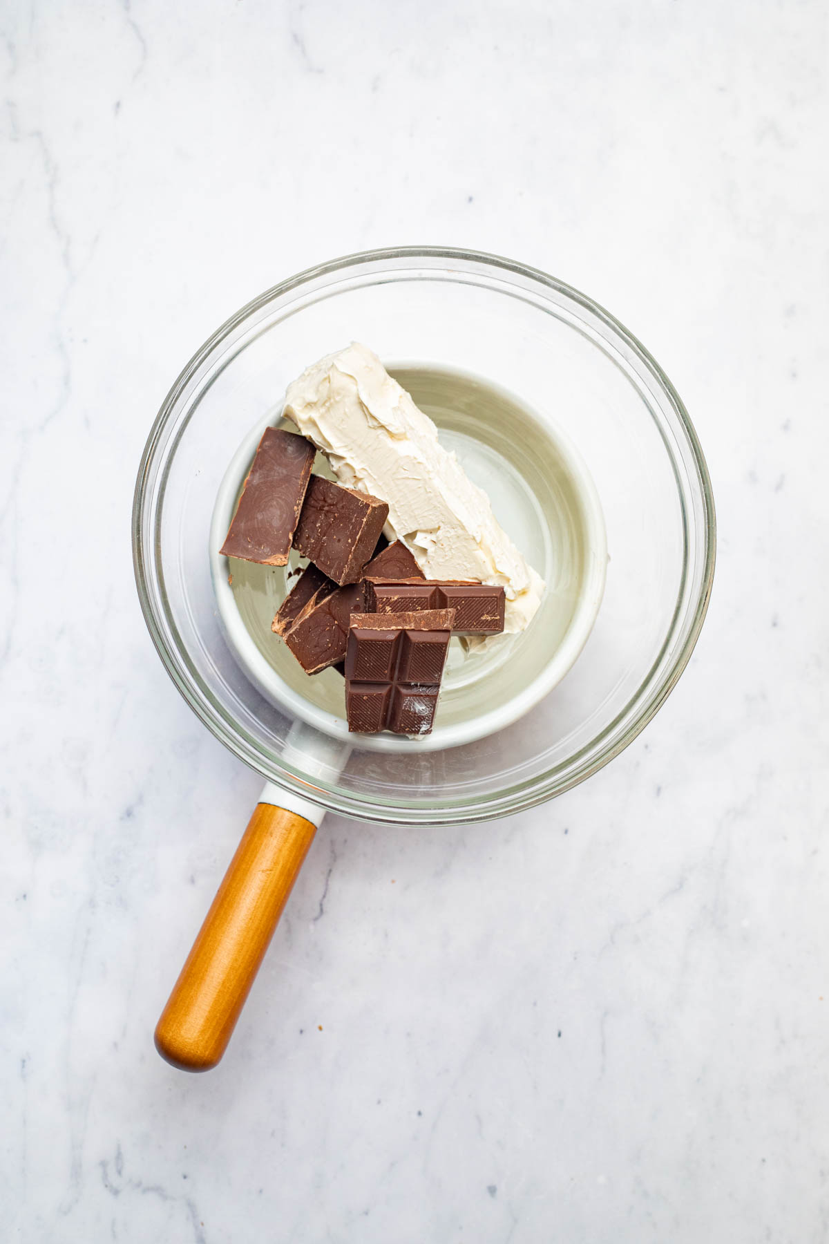 Vegan butter and dark chocolate, still solid in a glass bowl.