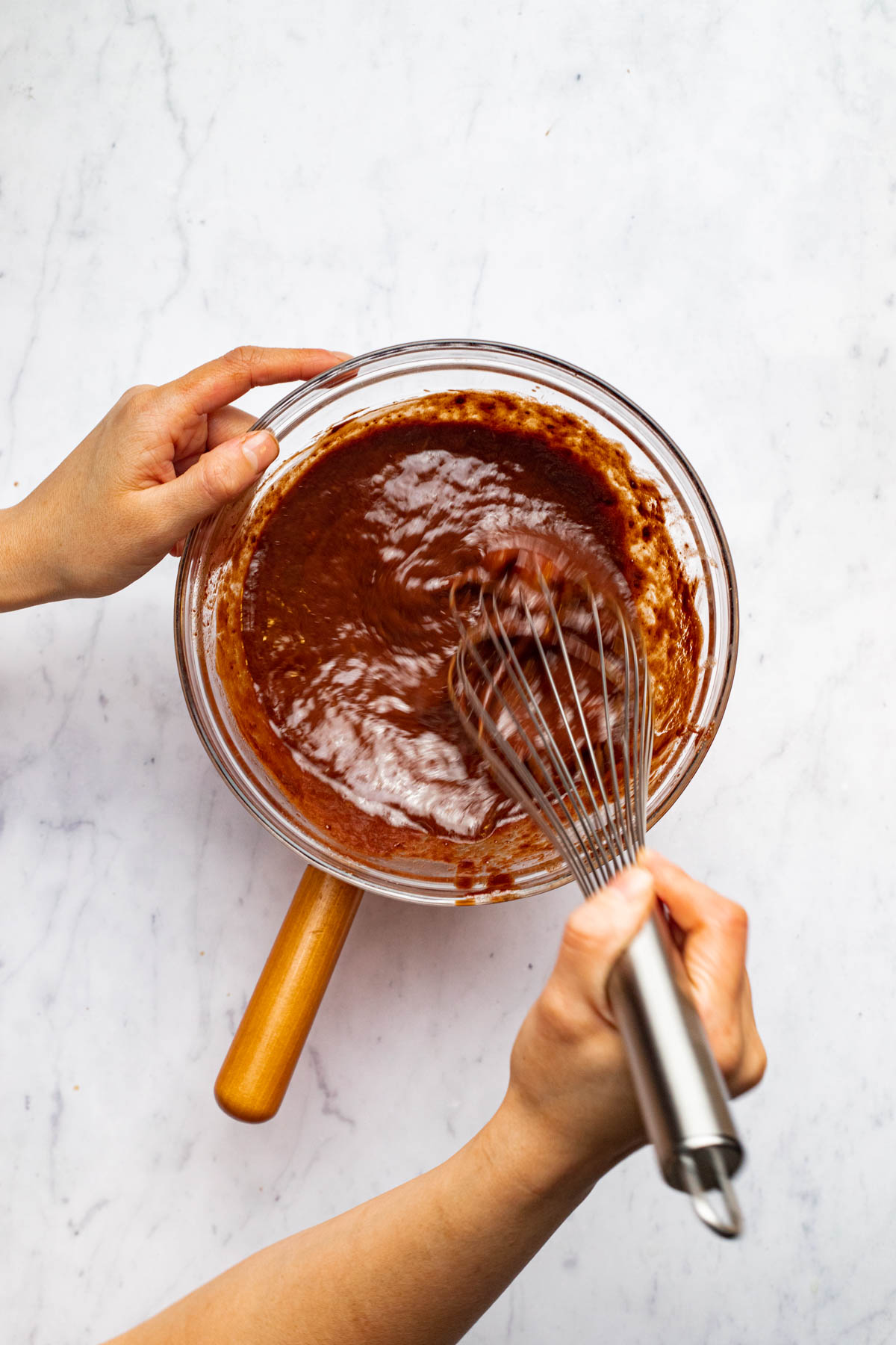 A hand whisking melted chocolate in a glass bowl.