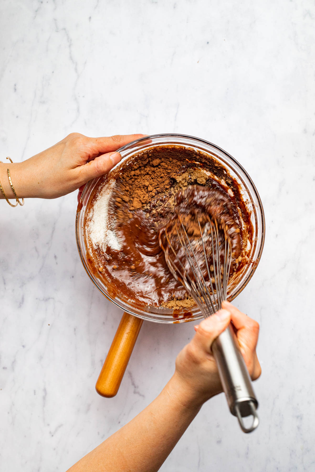 A hand whisking chocolate batter in a glass bowl.