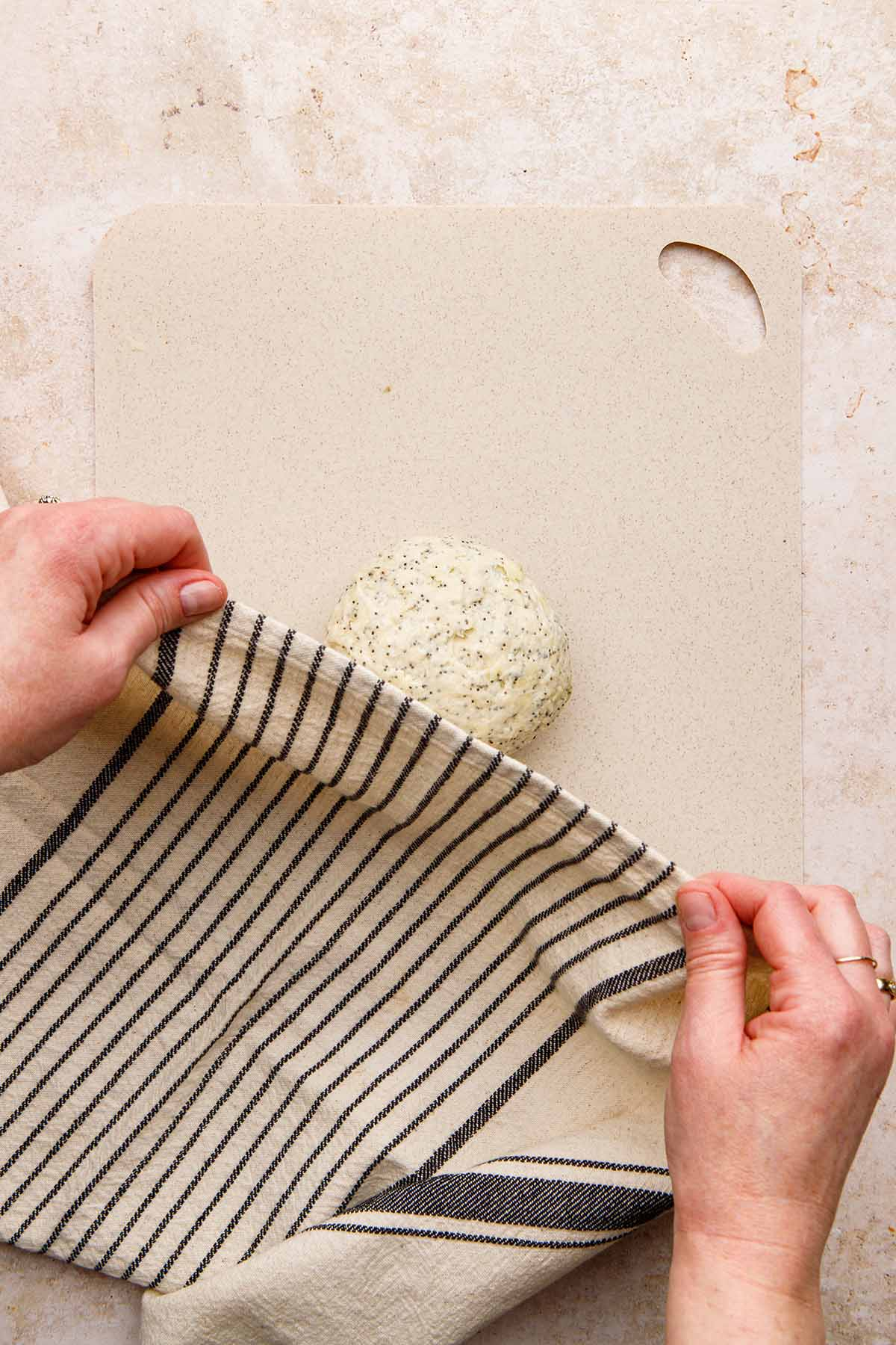 Hands covering a ball of dough with a striped tea towel.