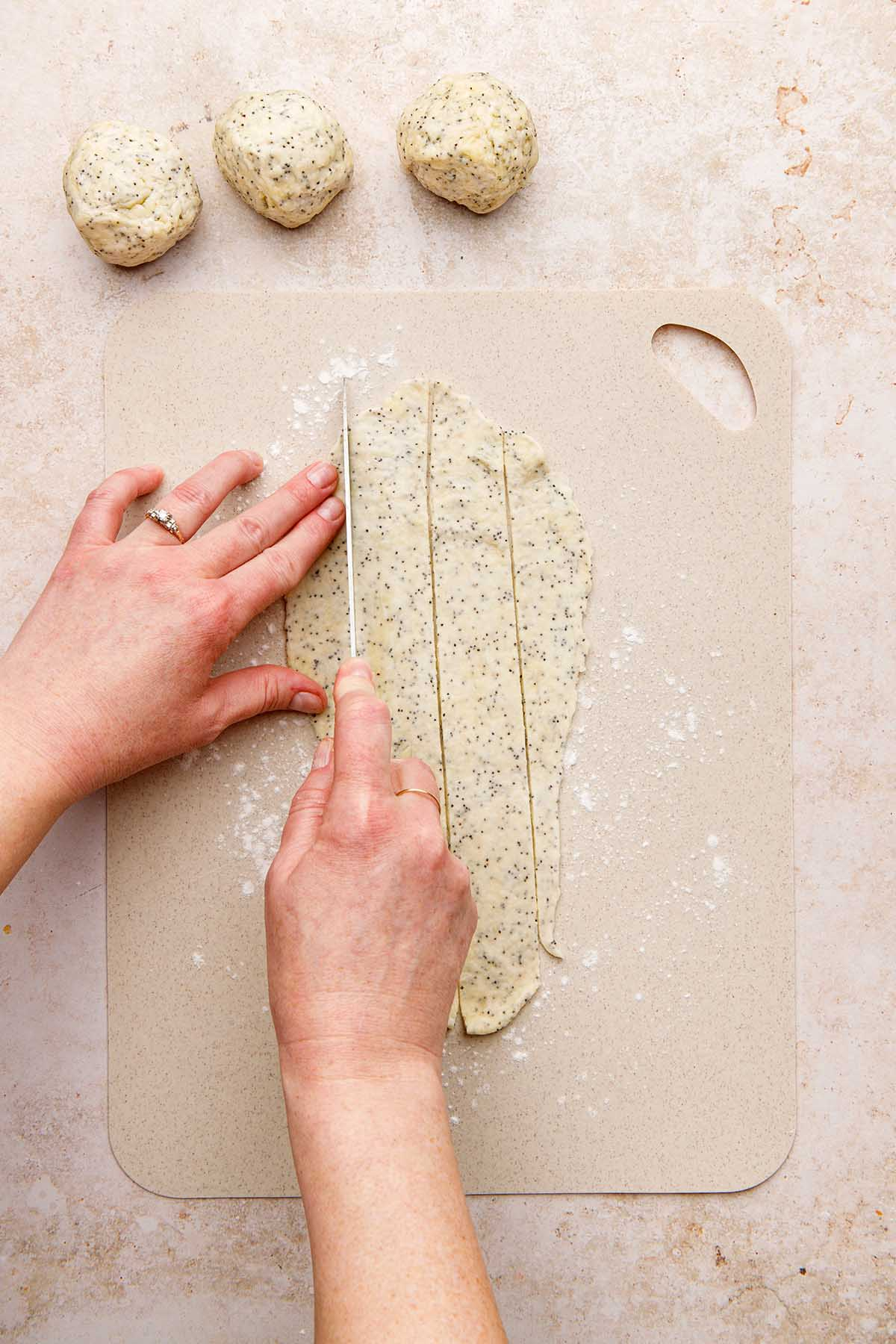 Hands slicing rolled out cracker dough with a knife.