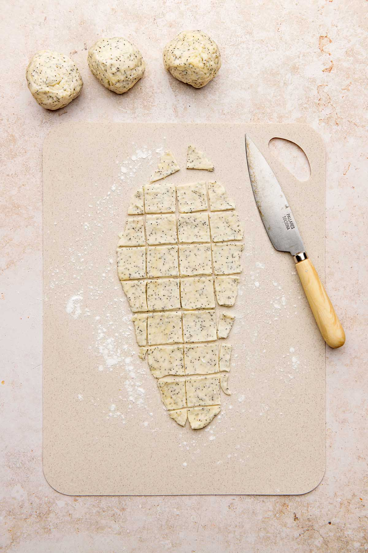 Rolled out cracker dough on a beige cutting board, sliced into pieces with a knife.