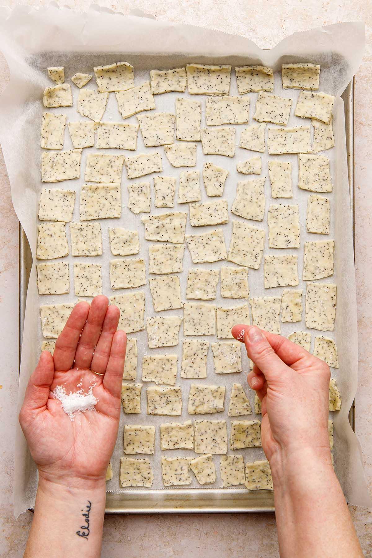 A hand sprinkling salt on unbaked crackers.