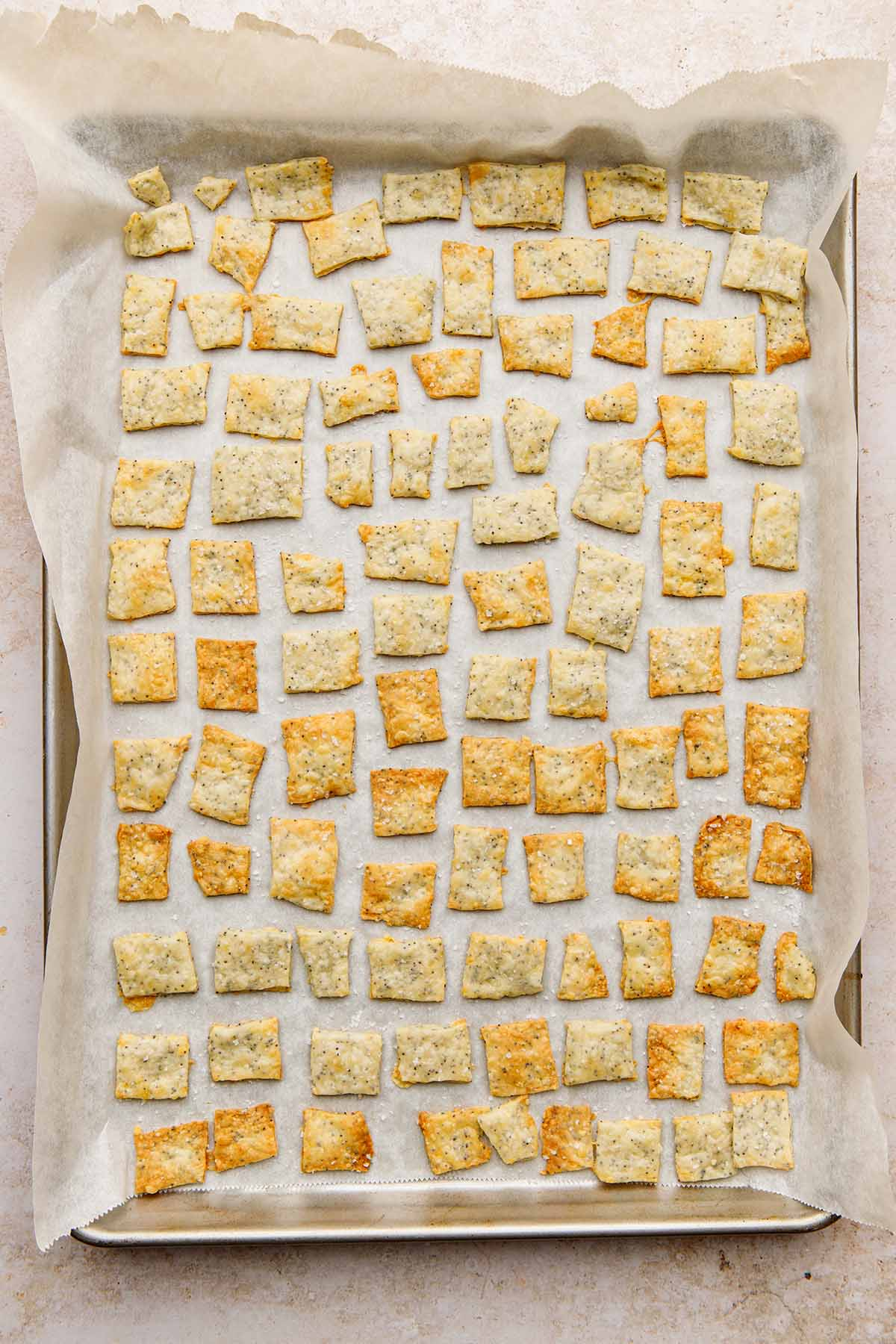 A baking tray lined with parchment paper filled with homemade white cheddar crackers.
