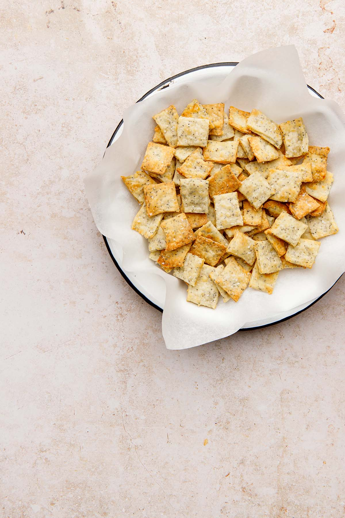 White cheddar crackers in a white dish lined with parchment paper.