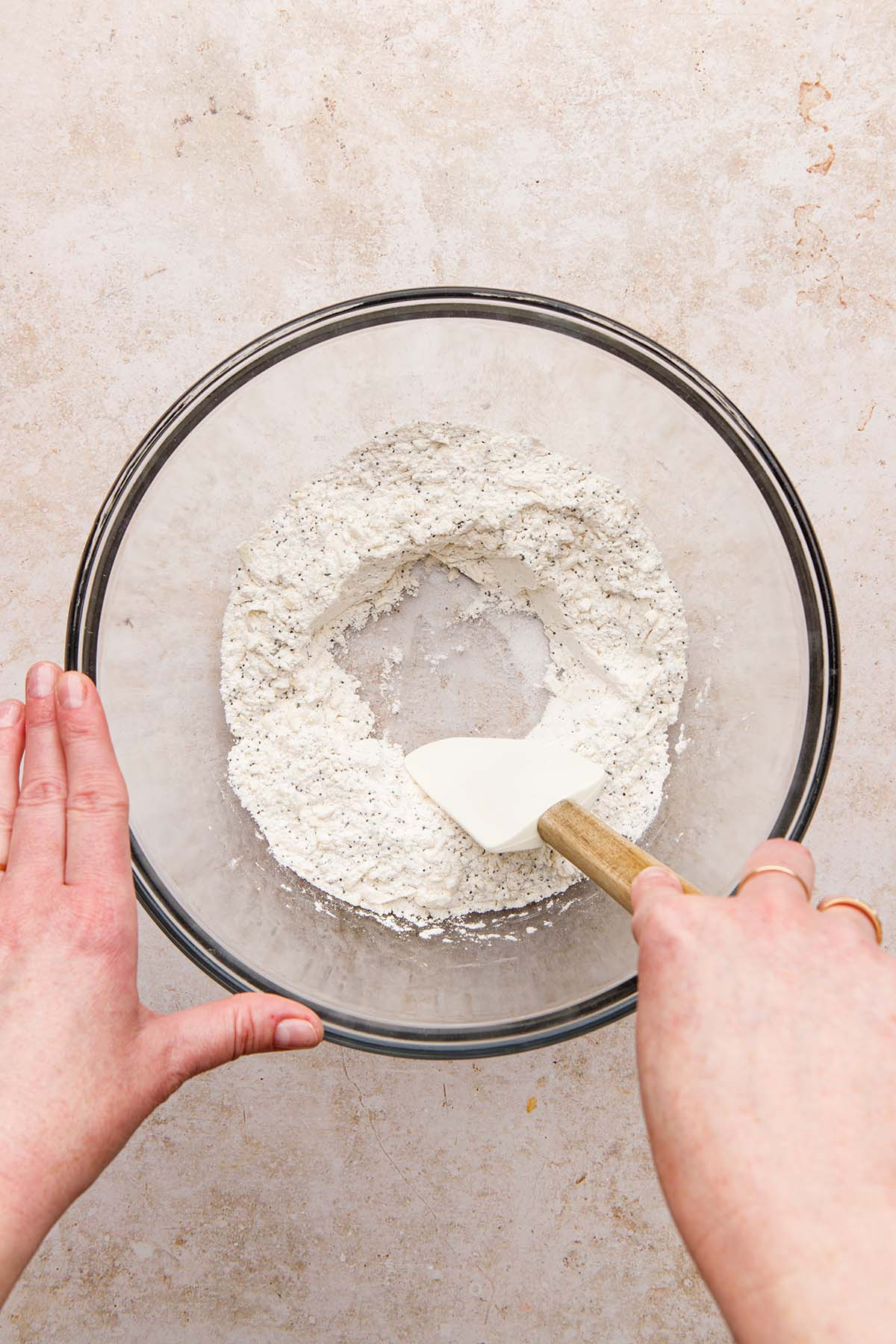 A hand using a rubber spatula to make a well in the middle of a bowl of flour.