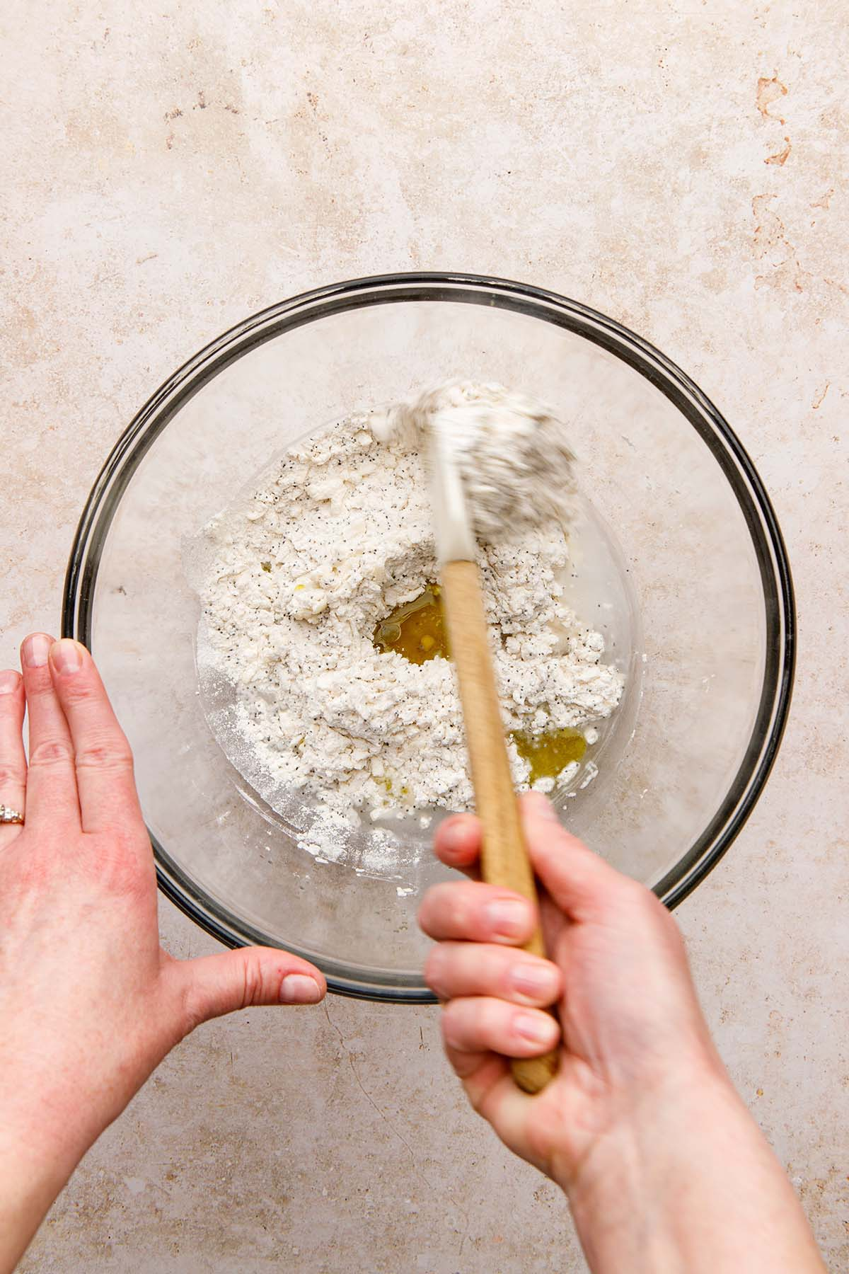 A hand mixing dough with a rubber spatula.