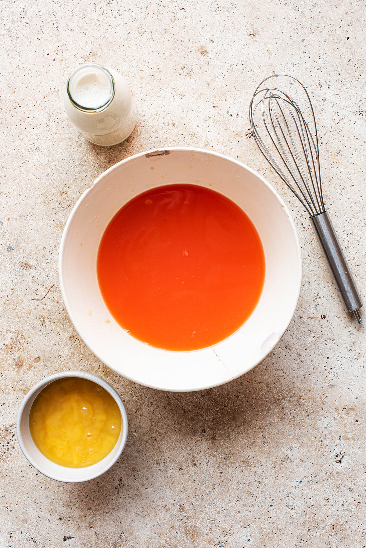 Orange juice in a large bowl with milk and honey around.