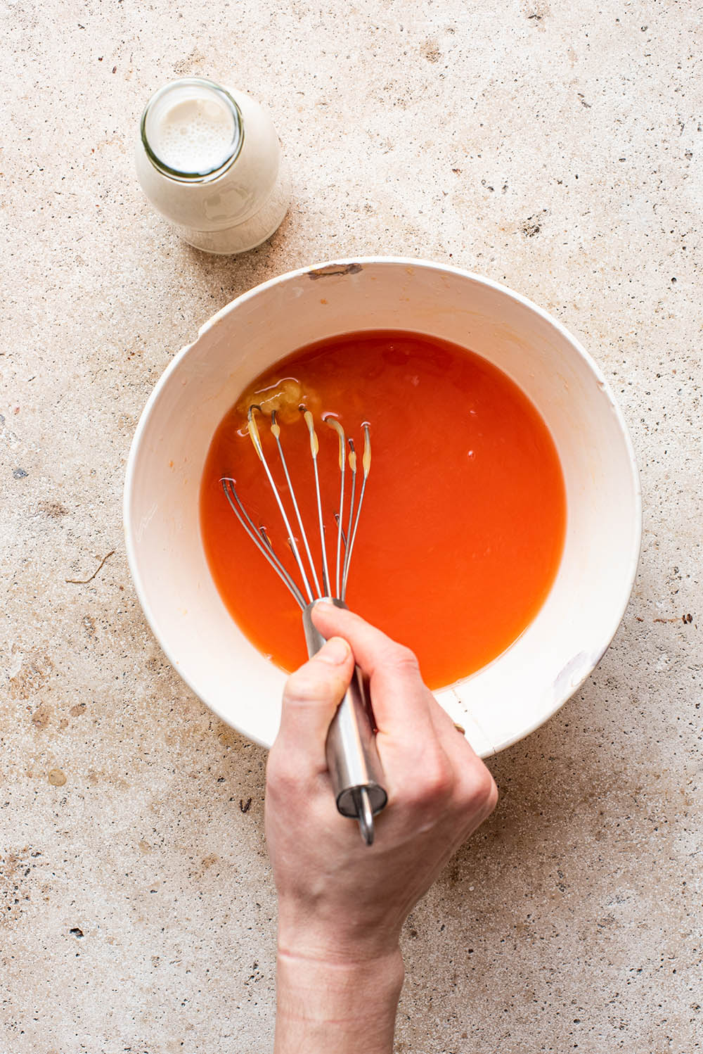 Honey being whisked in to the orange juice mixture.
