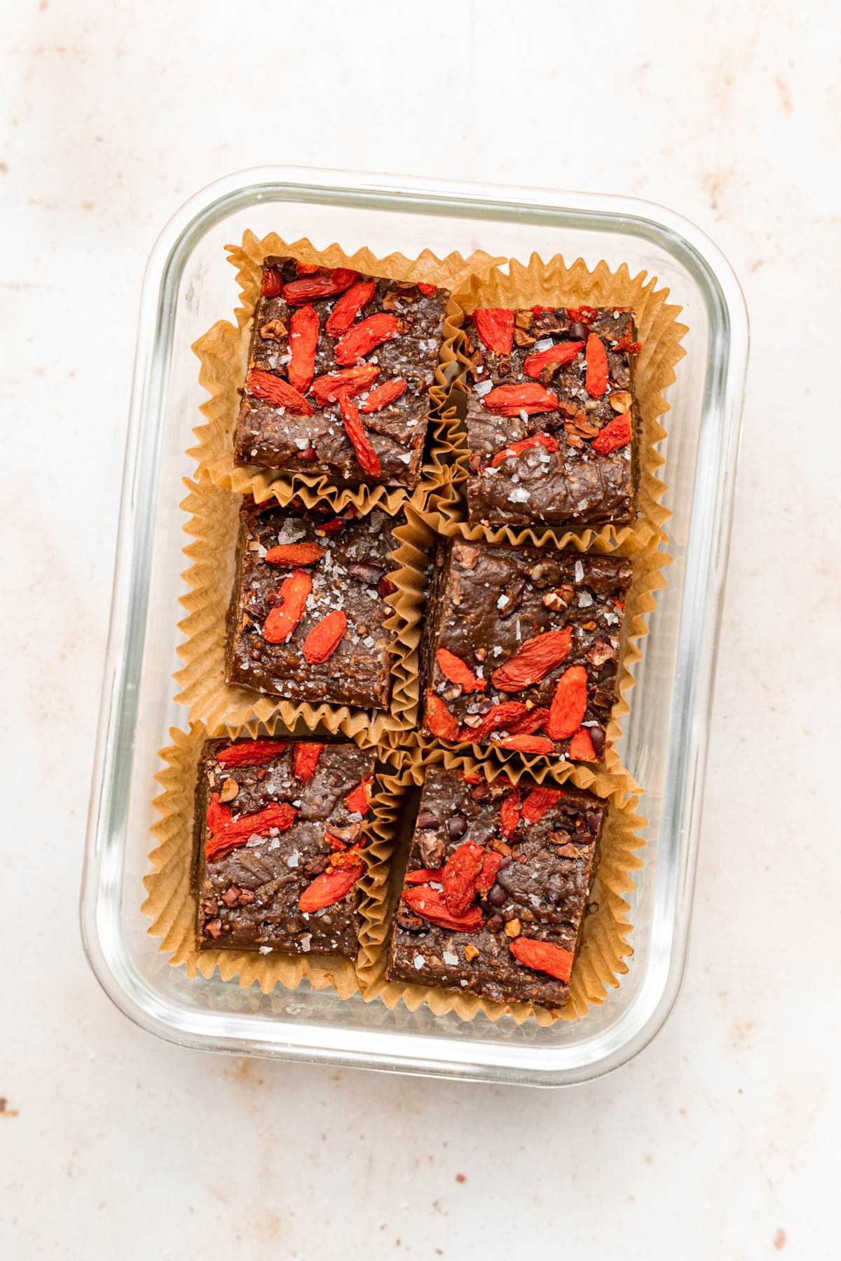 Fudge in small paper liners in a glass container.