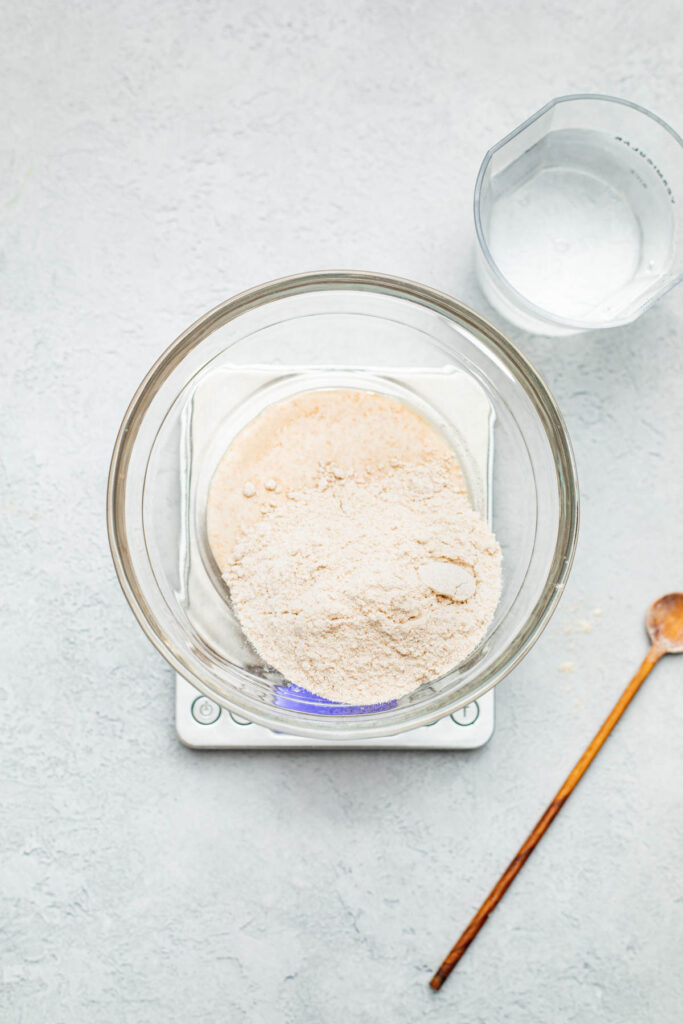 Unmixed flour and sourdough starter in a large glass bowl sitting atop a digital kitchen scale.
