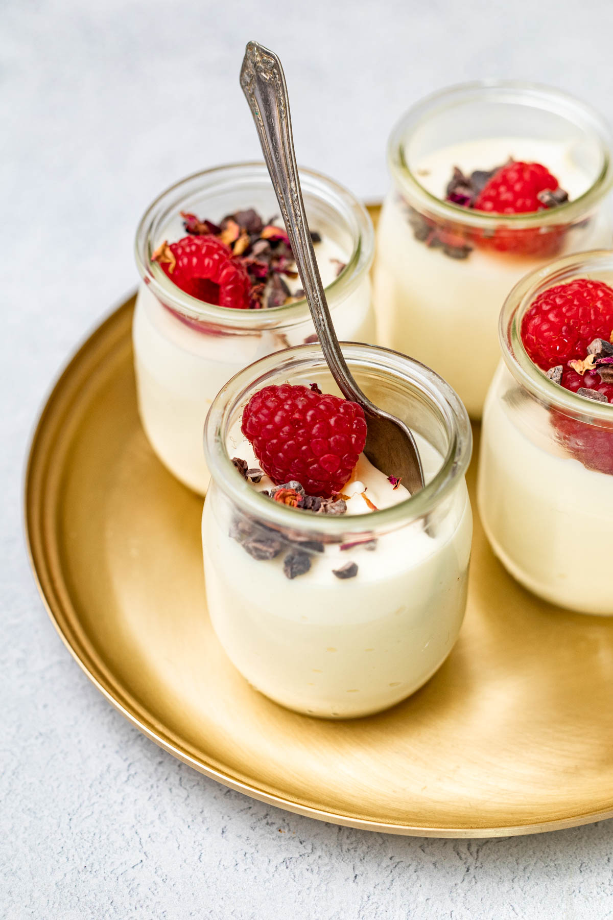 Jars of mousse garnished with cacao nibs, raspberries, and dried rose petals on top on a gold platter.