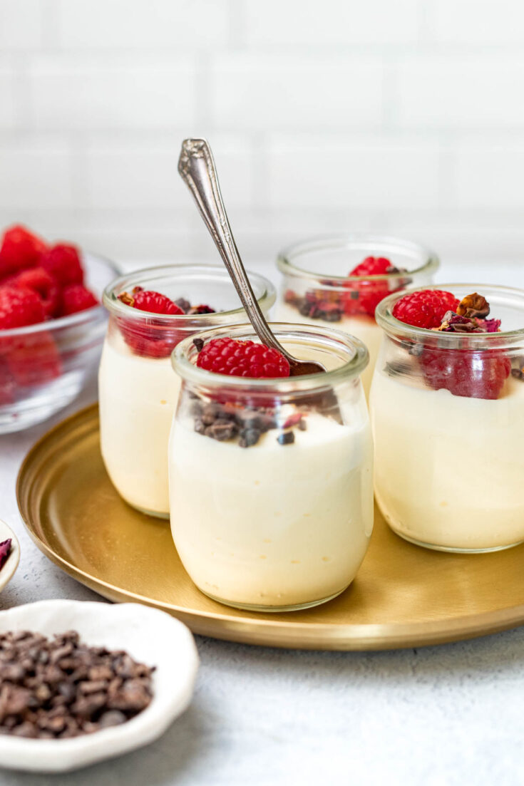 Jars of white chocolate mousse garnished with cacao nibs, raspberries, and dried rose petals on top.
