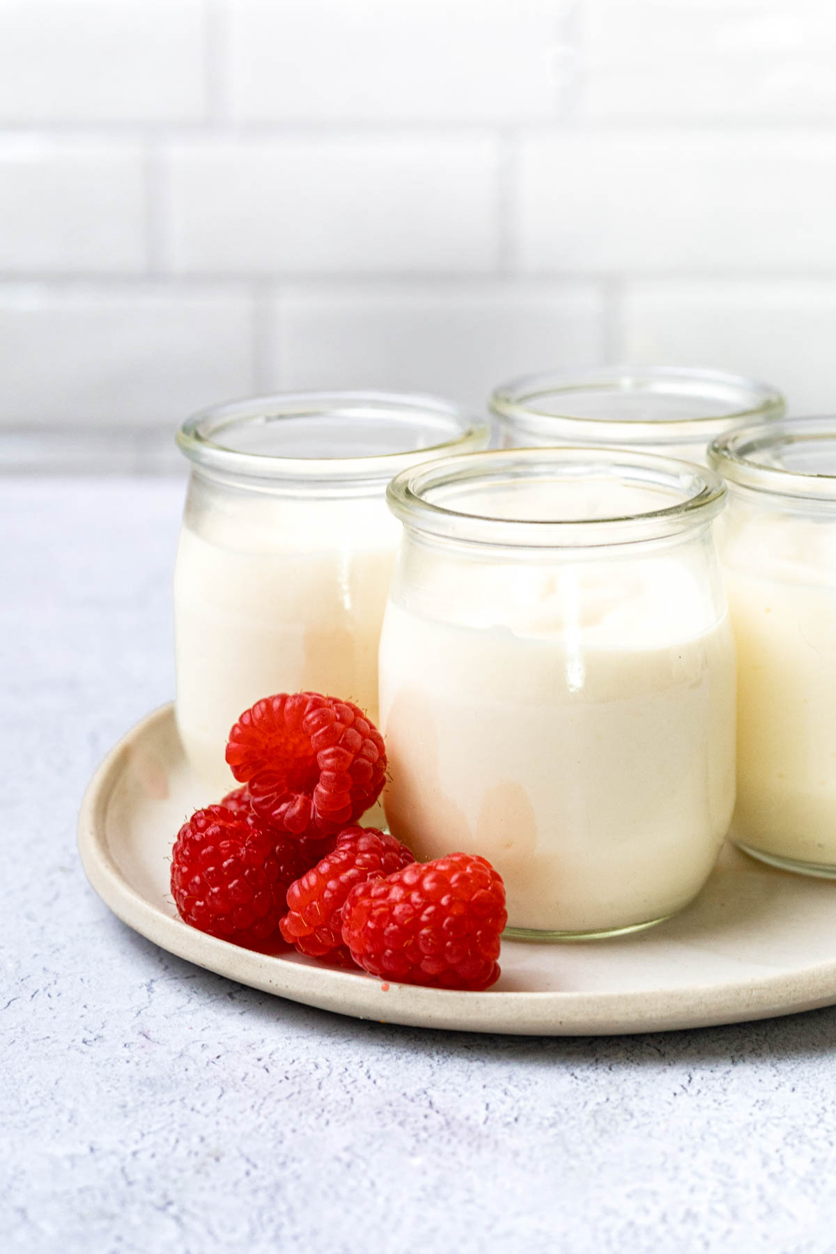 Jars of white chocolate mousse on a beige ceramic platter with fresh raspberries nearby.