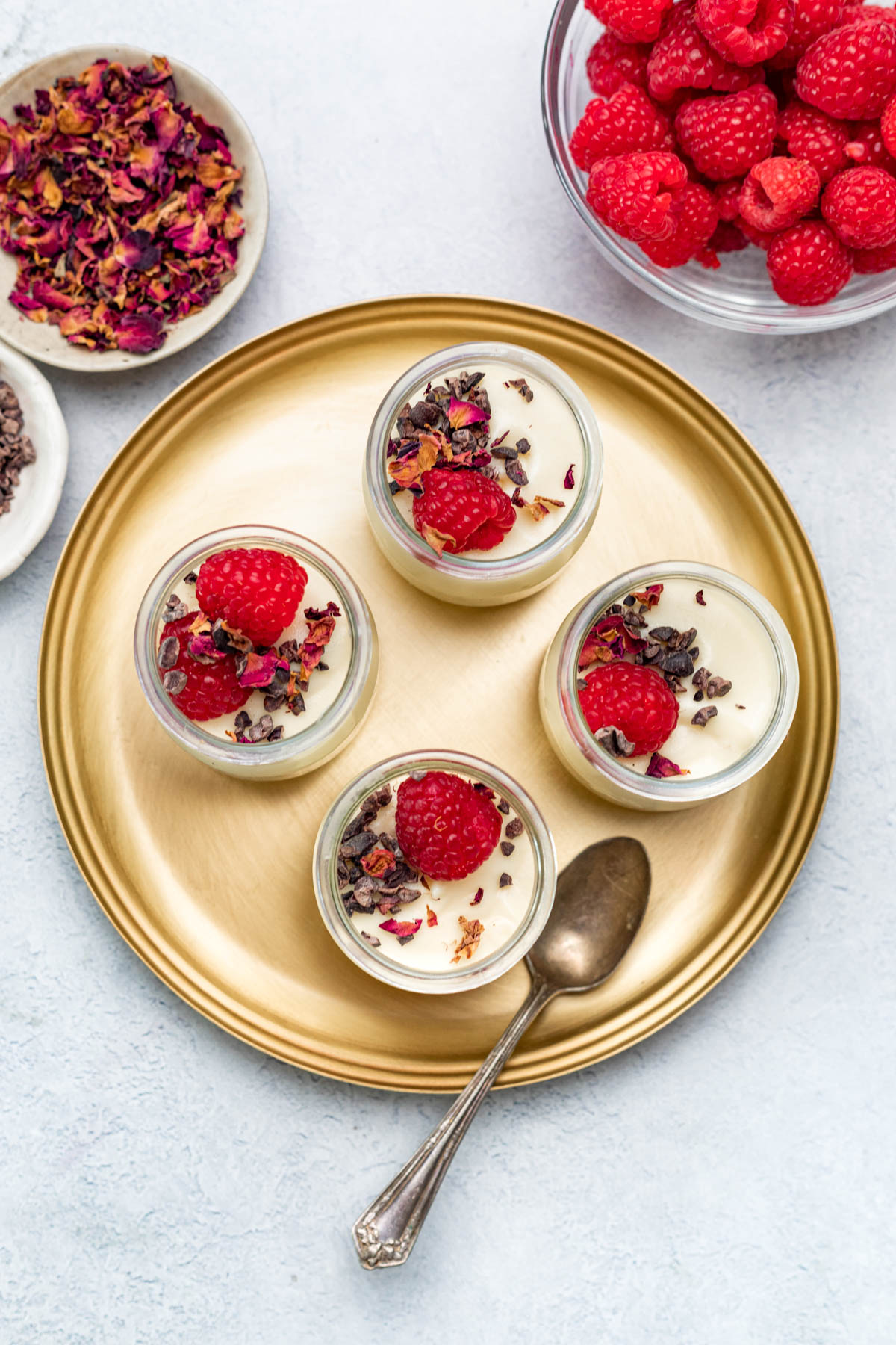 Overhead image of jars of desserts garnished with cacao nibs, raspberries, and dried rose petals on top.