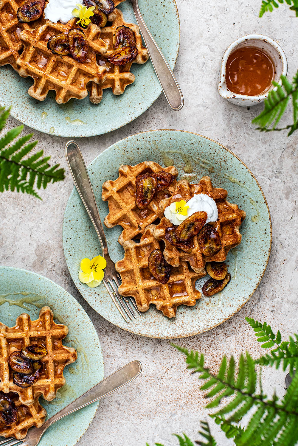 Three plates of waffles with ferns around the edges of the frame.