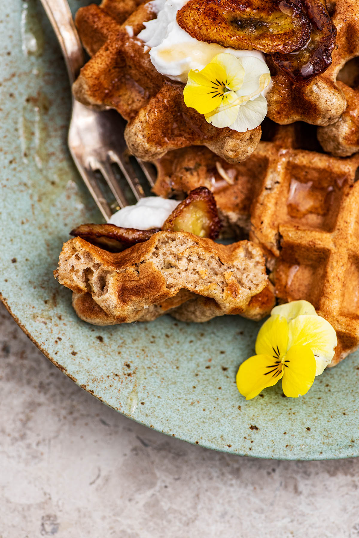 Close up of a piece of waffle on a fork to show interior texture.