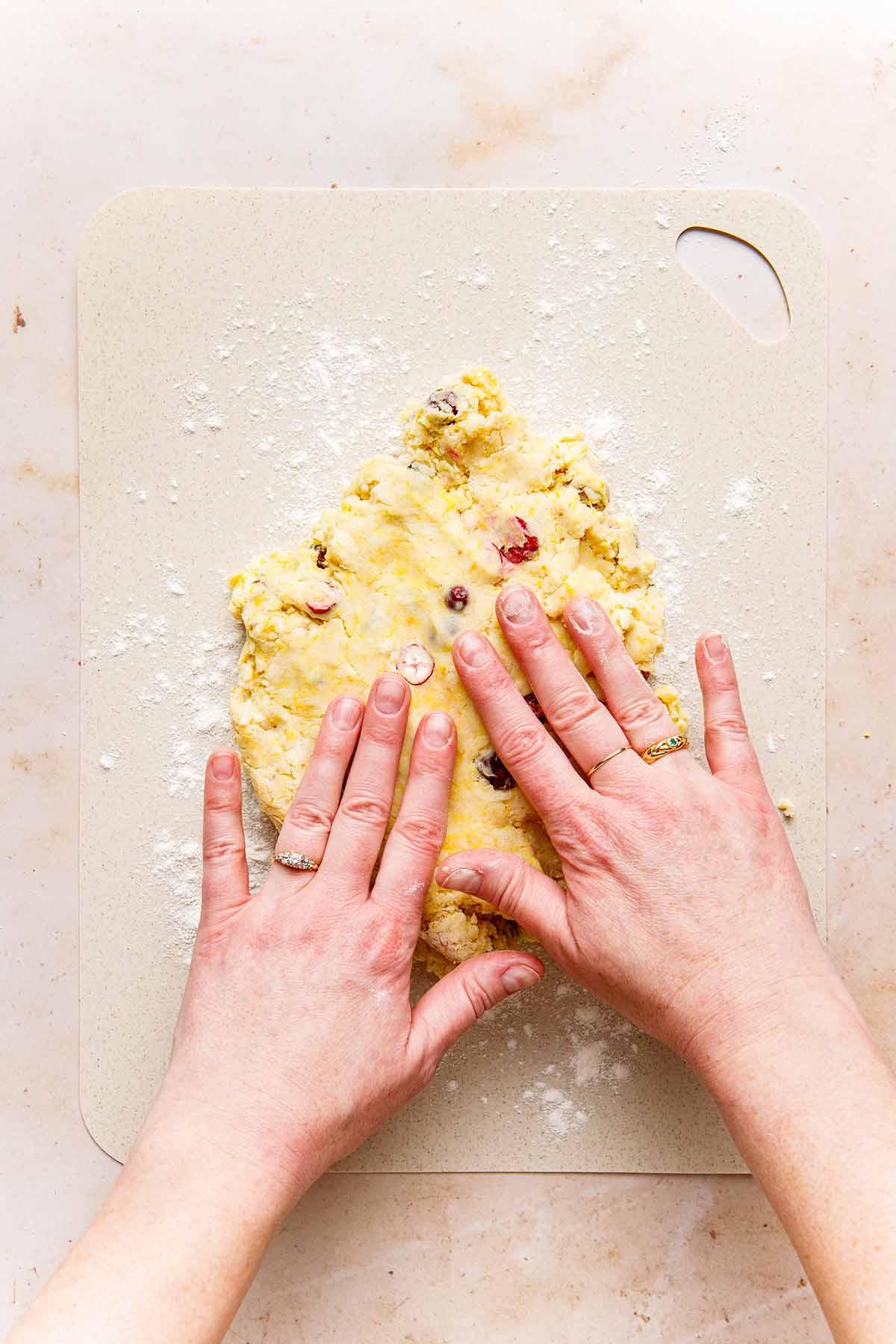 Hands pressing dough into a disc shape.