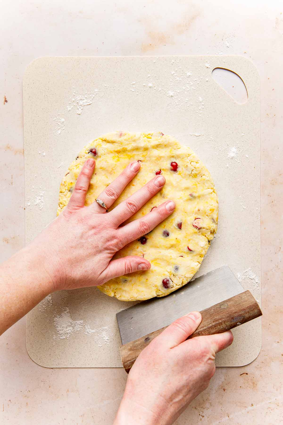 A hand using a bench scraper to smooth the edges of a disc of dough for orange cranberry scones.