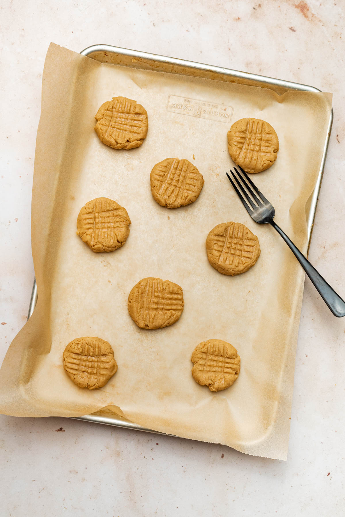 Cookies pressed with a fork for a crosshatch pattern.