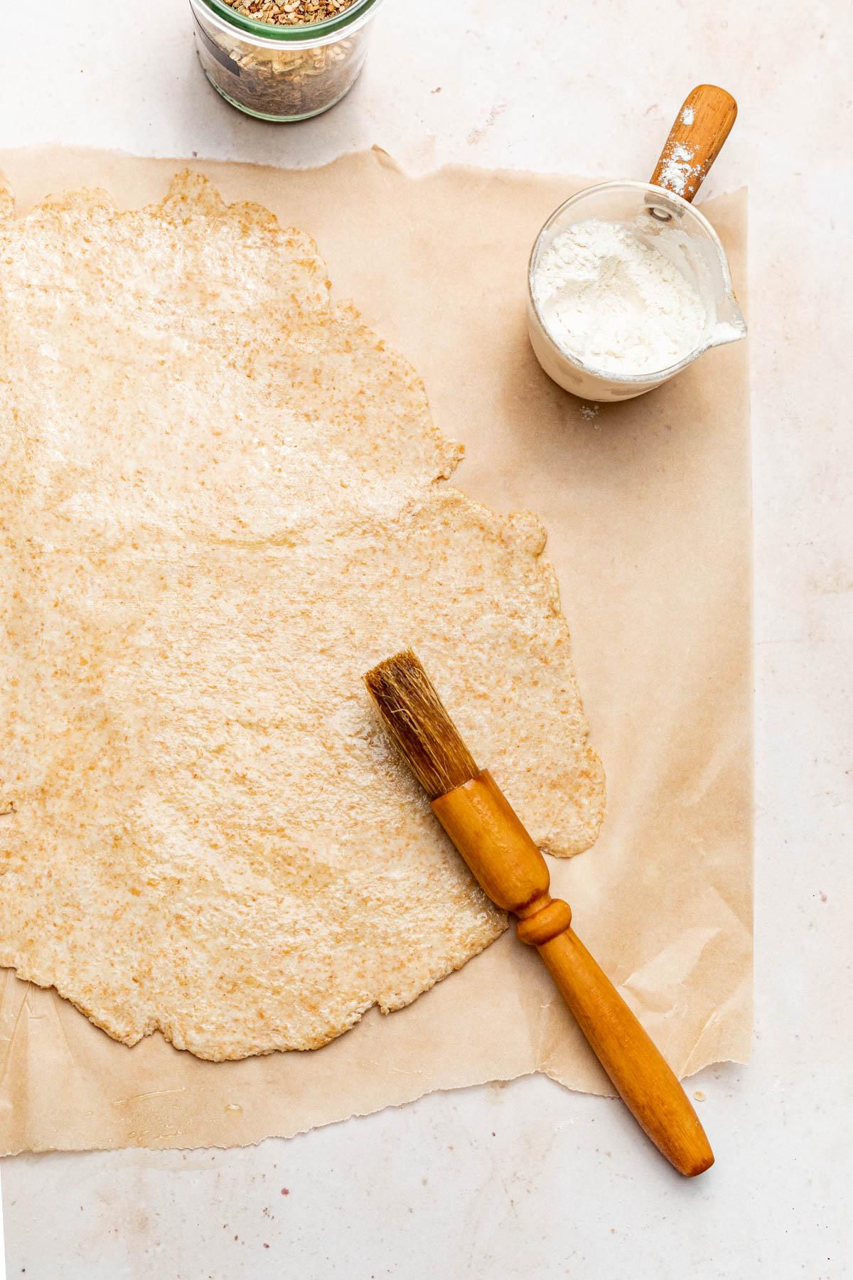 Brushing oil onto the cracker dough.