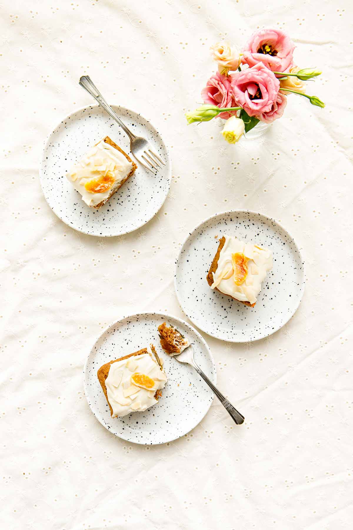 Iced squares of cake on small plates.