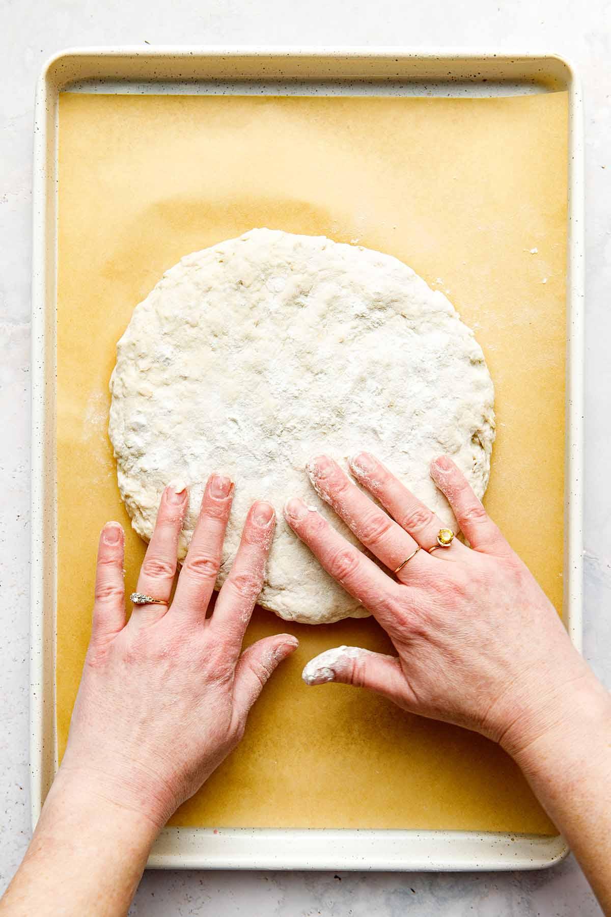 Woman's hands flattening the dough on a baking sheet.