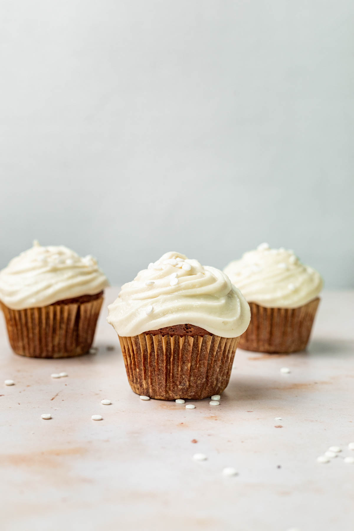Three chocolate cupcakes with vanilla buttercream frosting.