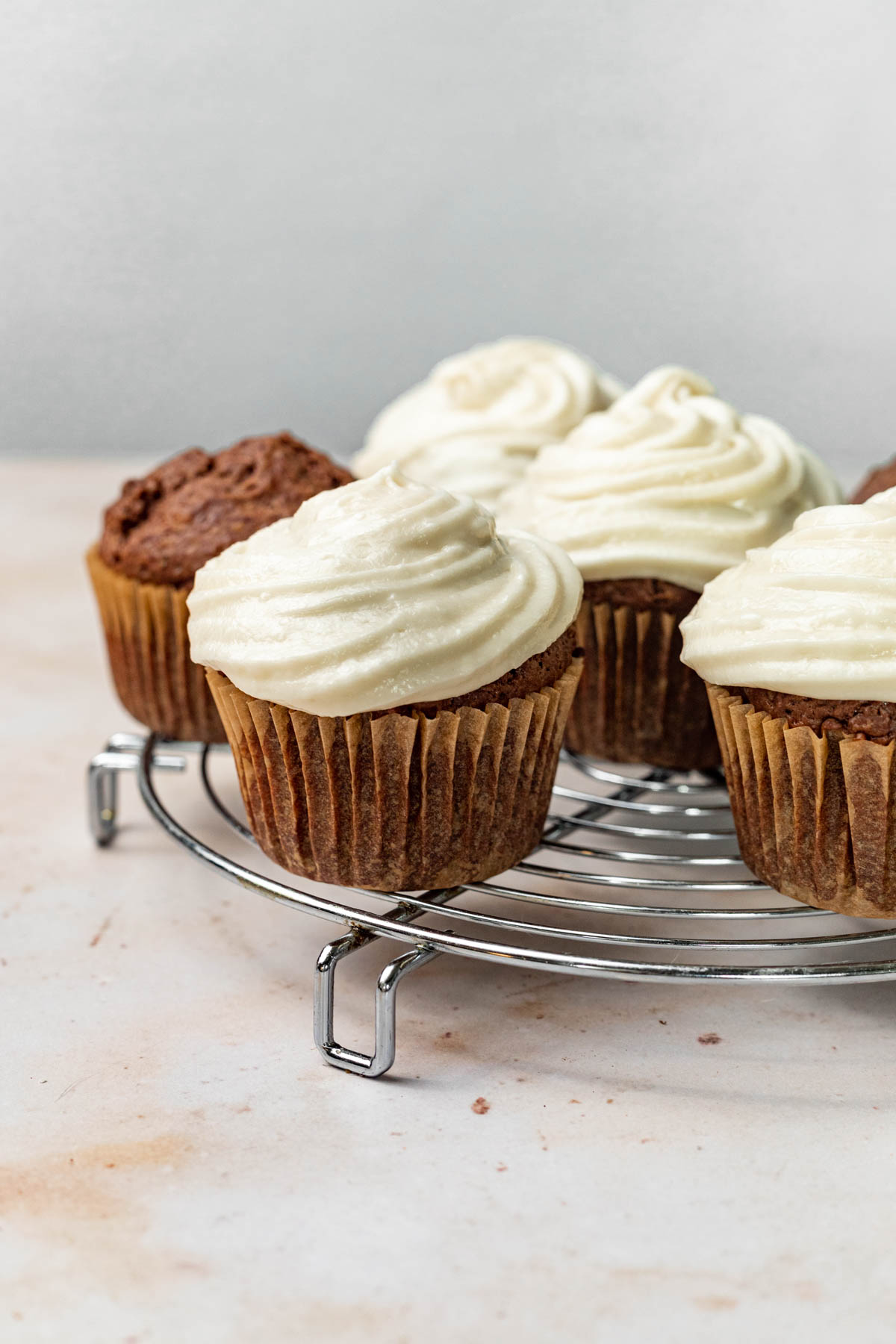 Cupcakes topped with frosting on a cooling rack.