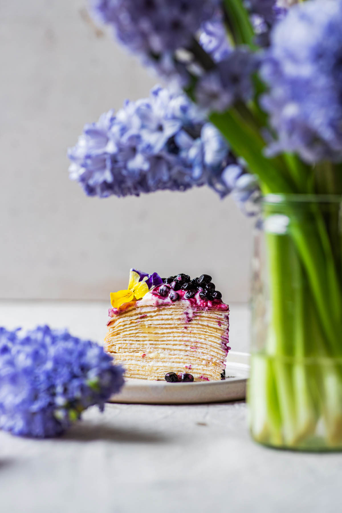 Cake slice with hyacinth in forefront.