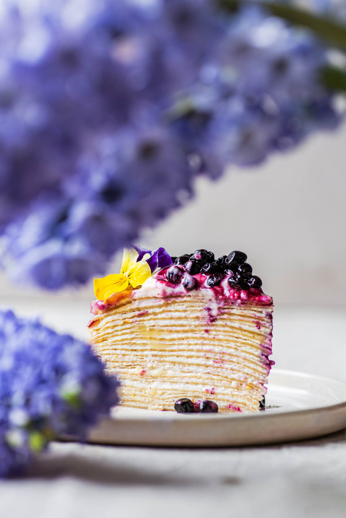 Slice of cake with flowers in forefront.