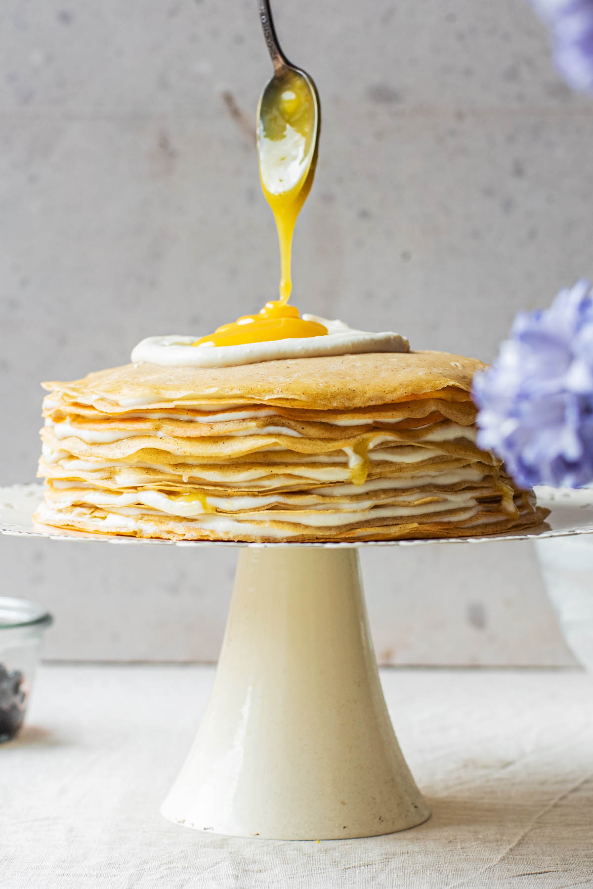Drizzling lemon curd over the top of the crepe cake.
