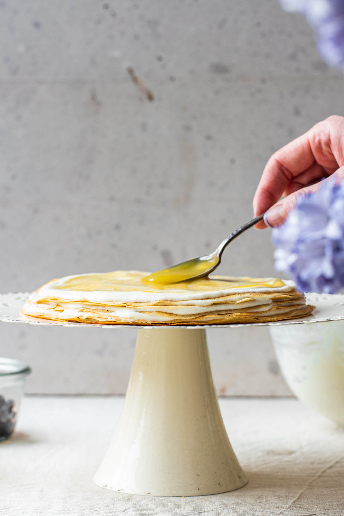 Spreading lemon curd onto layered crepes.