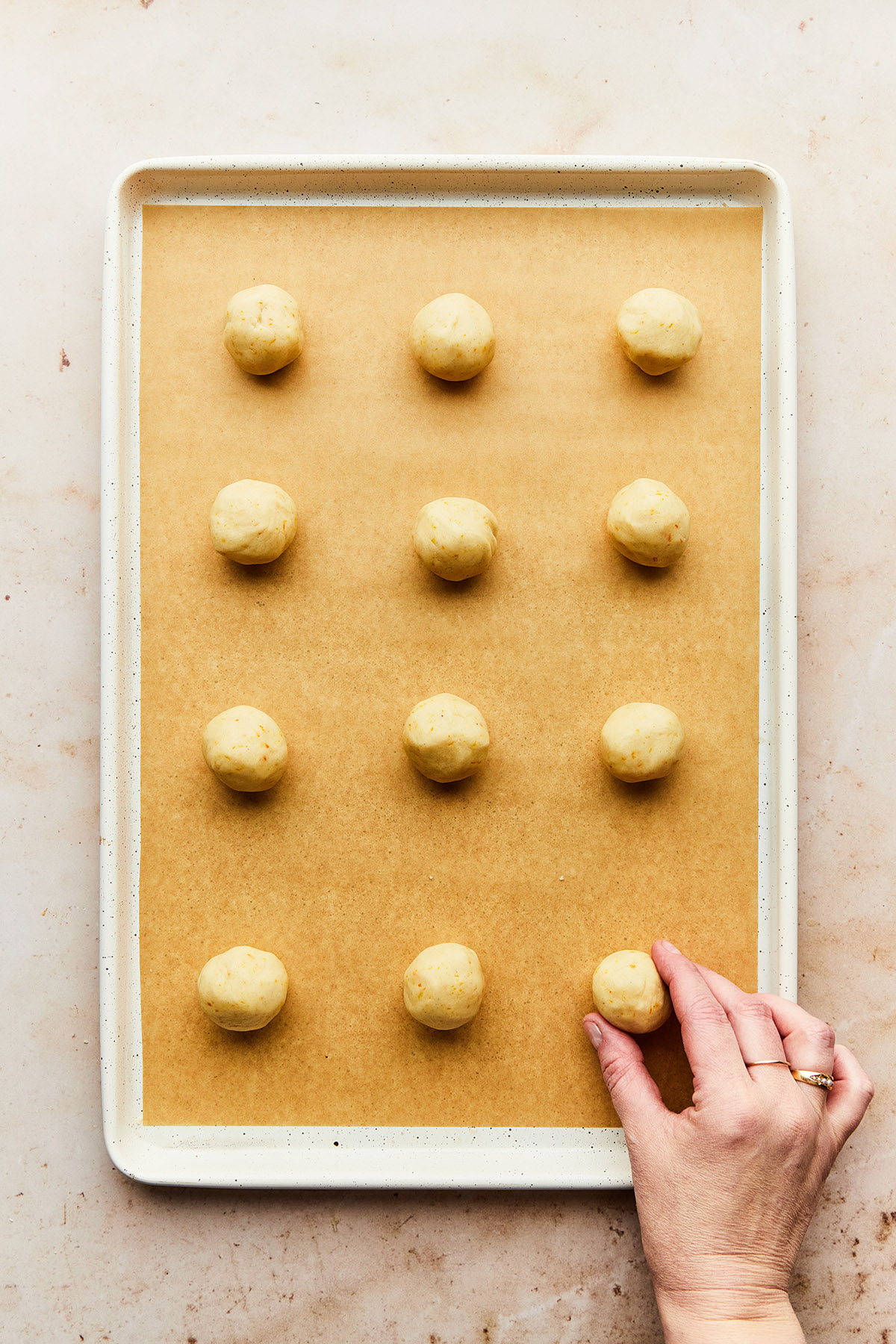 A hand placing the last of 12 unbaked Mexican wedding cookies on a baking sheet.