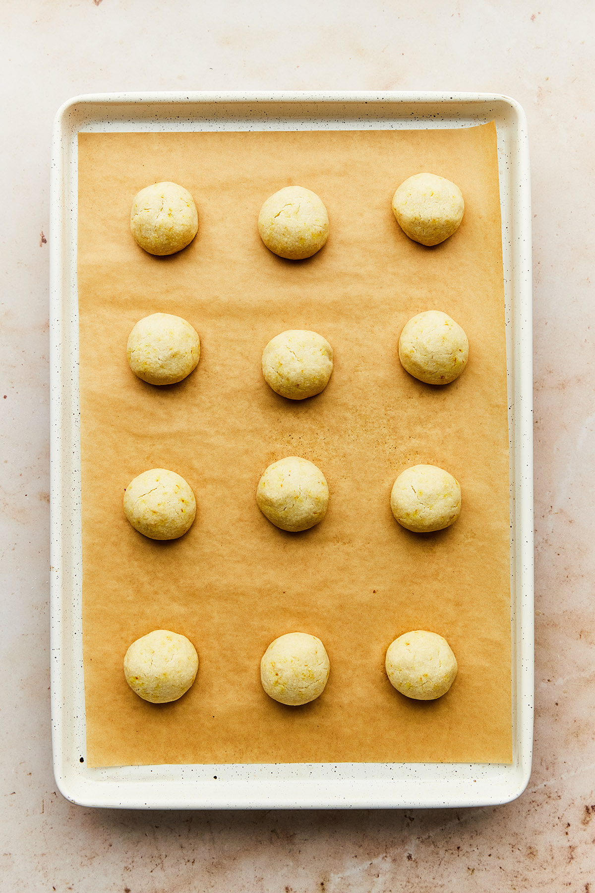 Small round baked cookies on a baking sheet lined with parchment paper.