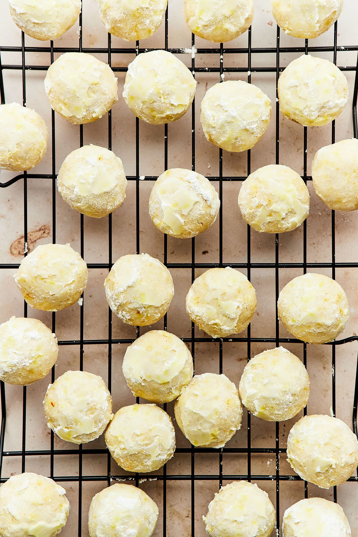 Close up overhead of Mexican wedding cookies which have been rolled in powdered sugar while warm to create a light glaze on the cookies.