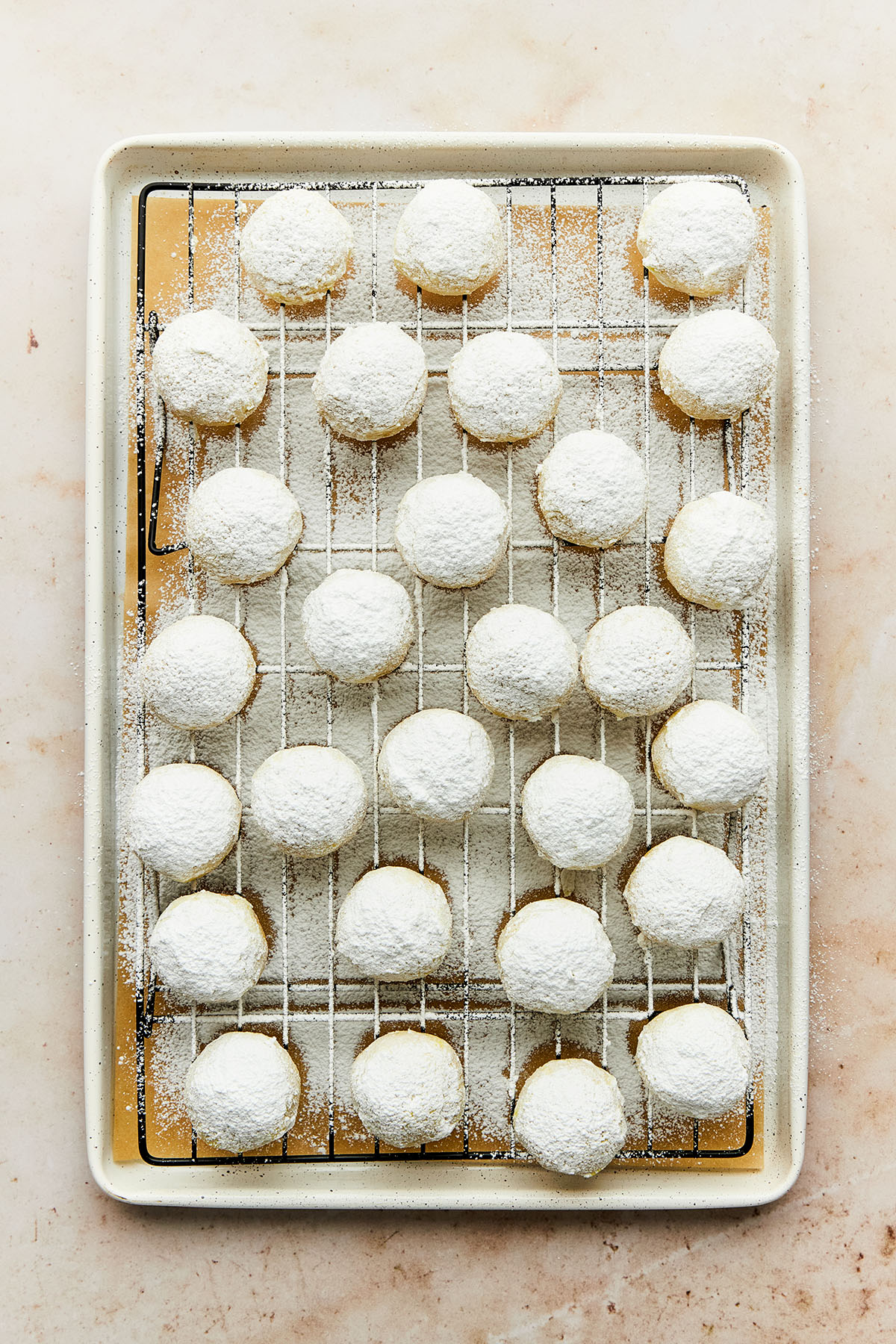 Overhead image of a tray of small round cookies coated with powdered sugar.
