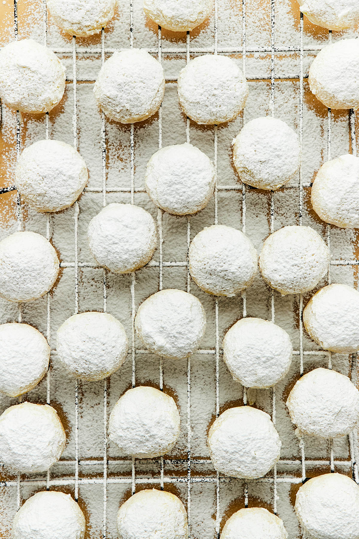 Close up of a tray of Mexican wedding cookies dusted with powdered sugar.