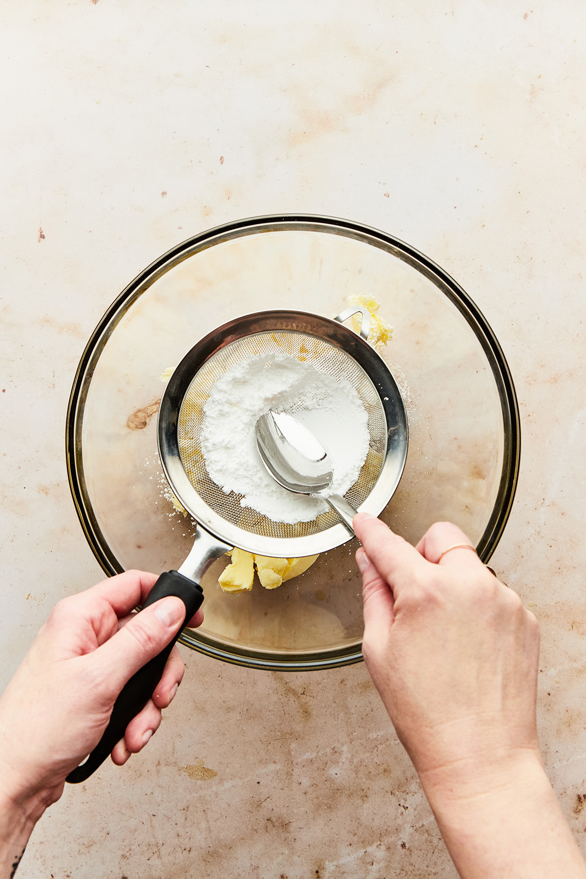 A hand sifting icing sugar into a bowl of butter by pressing it through a sieve using the back of a spoon.