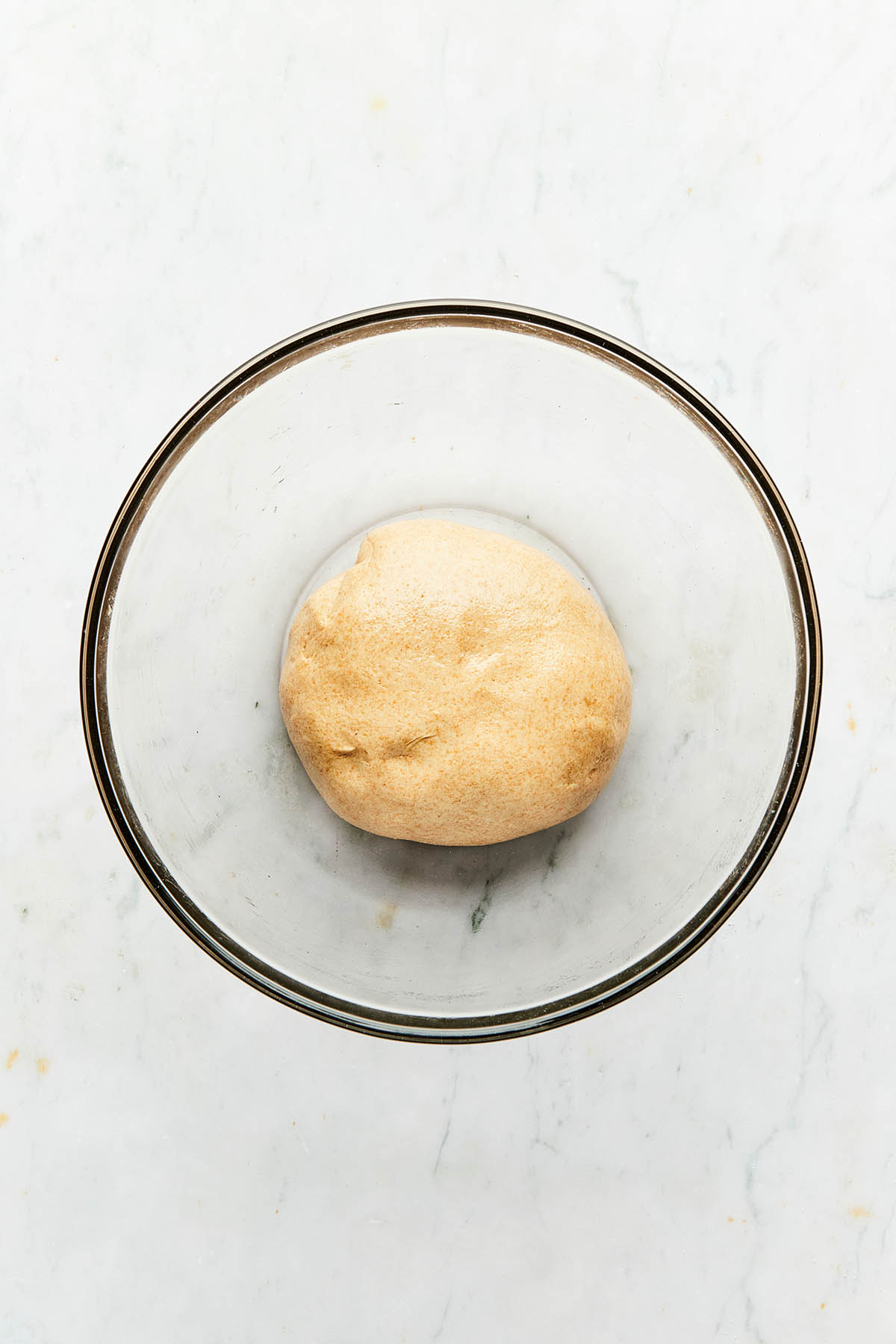 A ball of pizza dough in a glass bowl.