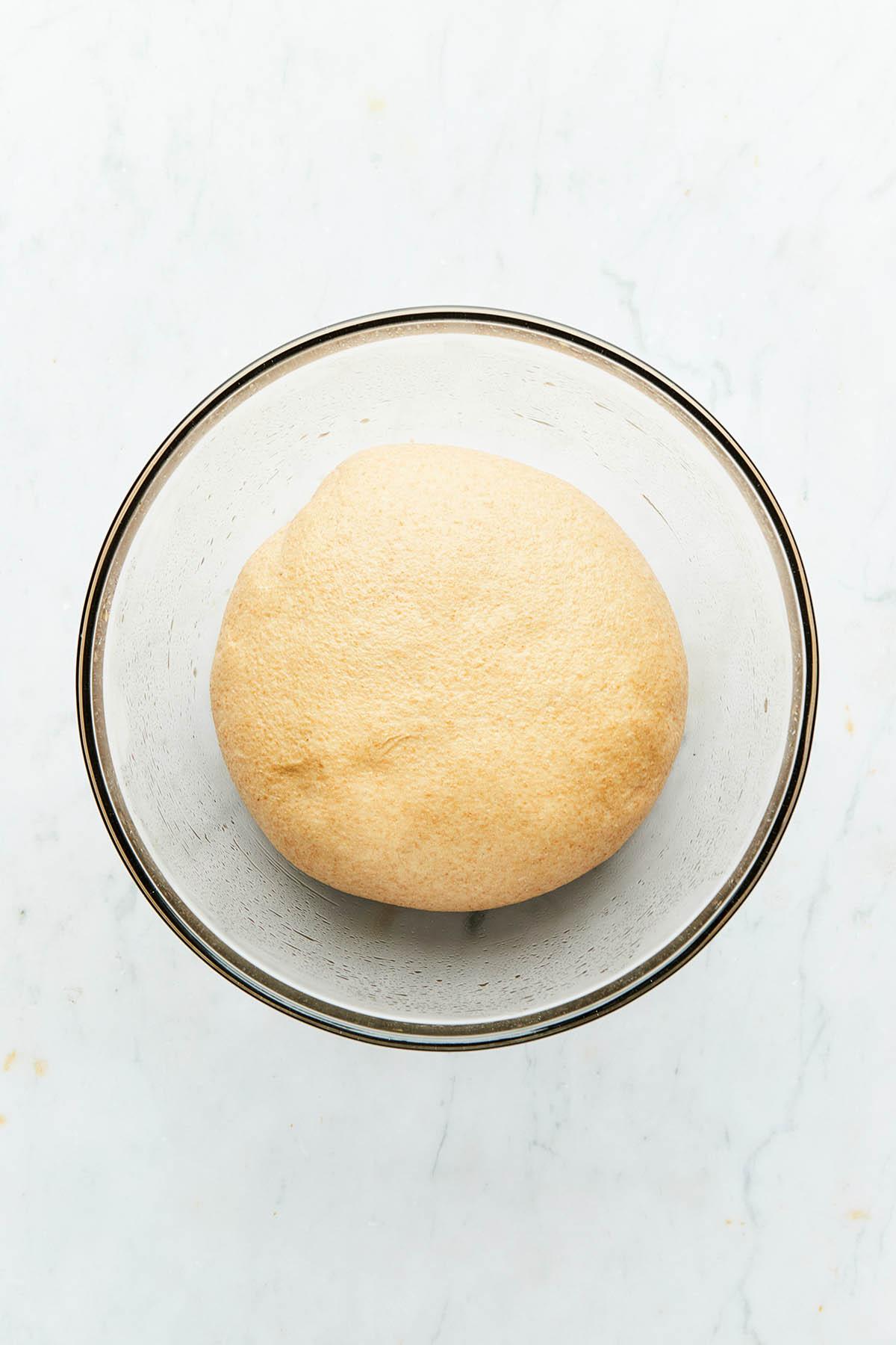 Risen pizza dough in a glass bowl.