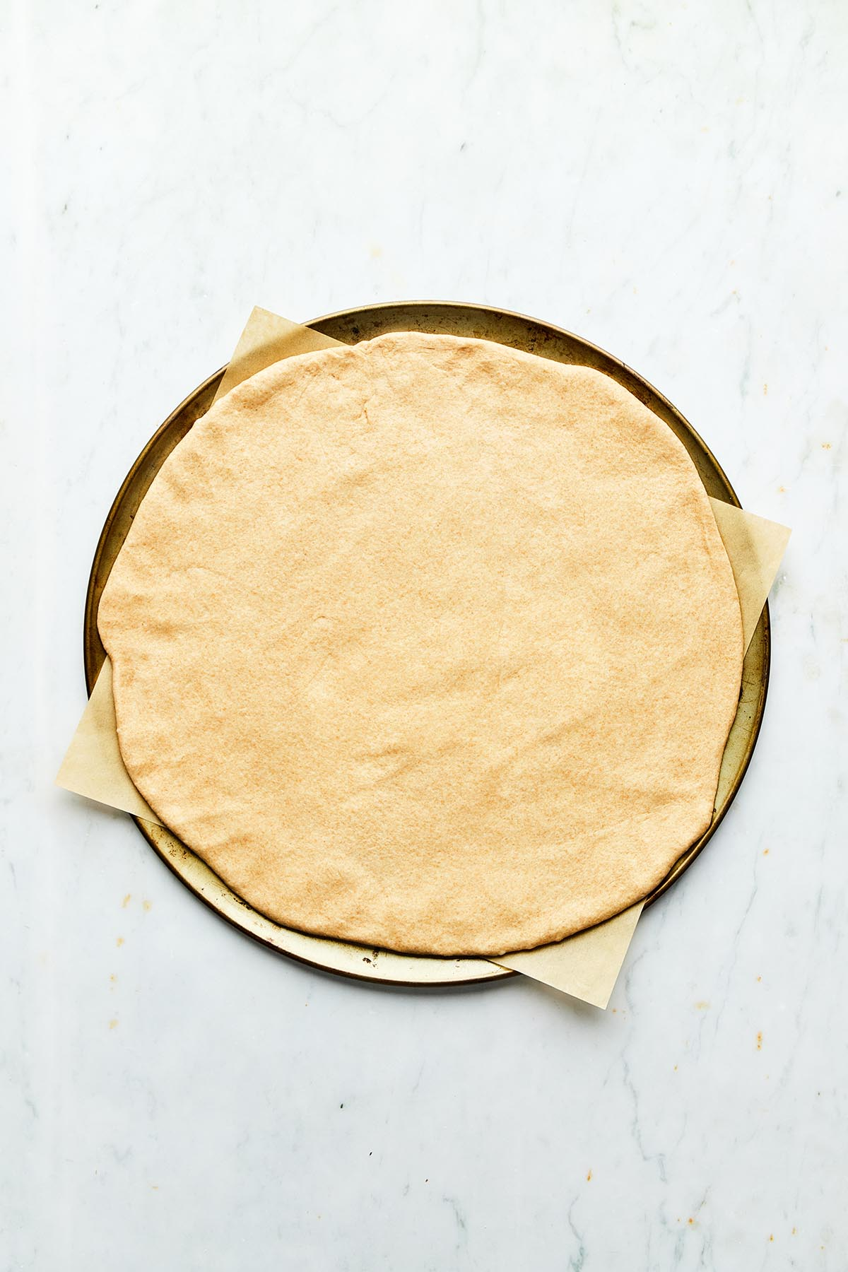 Round rolled out pizza dough on a baking tray lined with parchment.